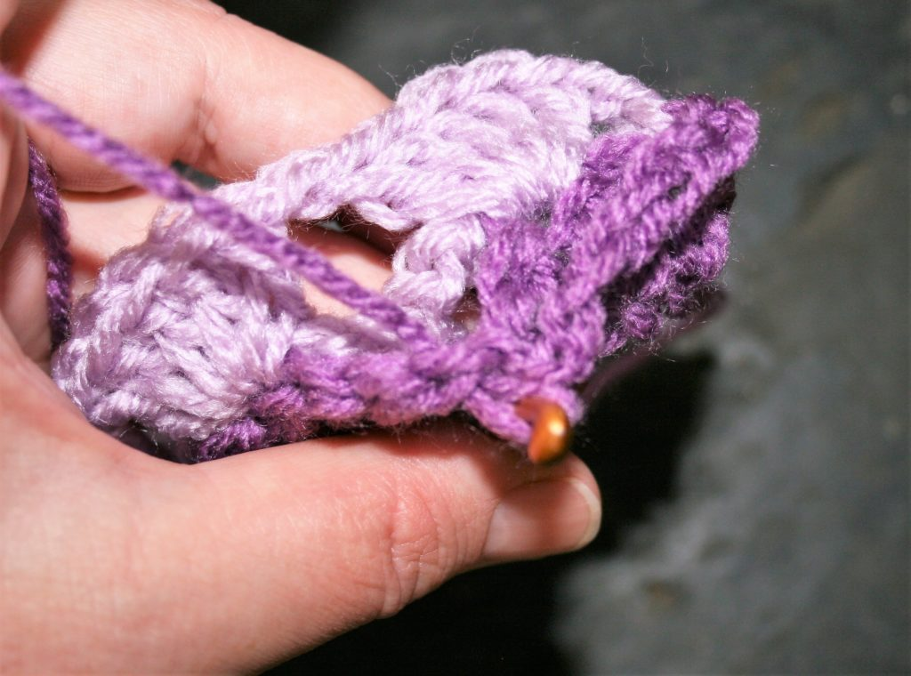 Single crochet in the chain 1 space between the double crochets of the same color